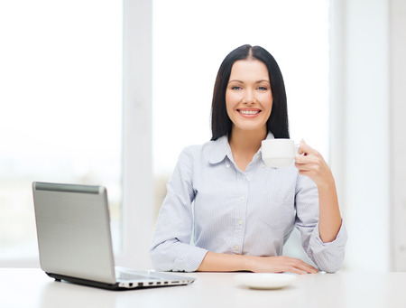 education, business and technology concept - smiling businesswoman or student with laptop computer and coffee photo