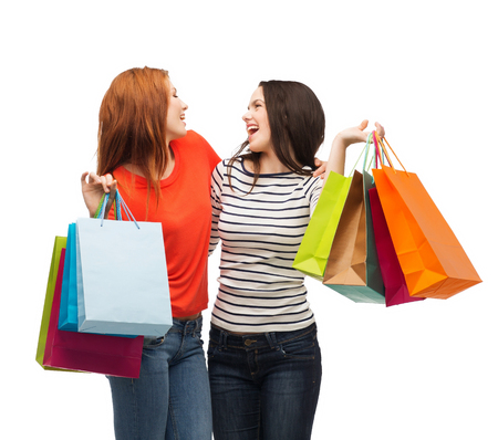 shopping, sale and gifts concept - two smiling teenage girls with shopping bags photo