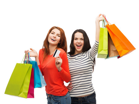 shopping, sale and gifts concept - two smiling teenage girls with shopping bags and credit card photo