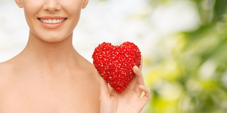 health, beauty and charity concept - beautiful woman with red heart
