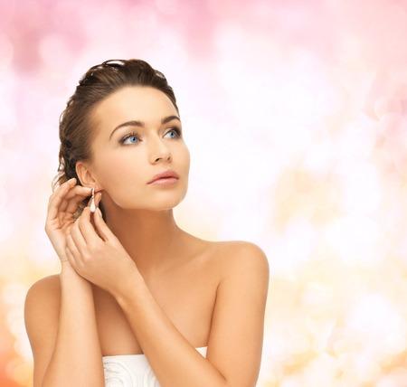 earrings: beauty and jewelry concept - beautiful woman wearing shiny diamond earrings