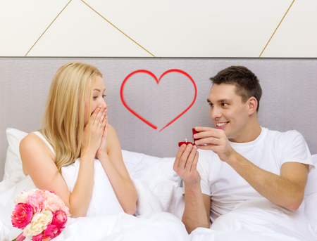 hotel, travel, relationships, holidays and happiness concept - man givnig woman little red box and ring in it photo