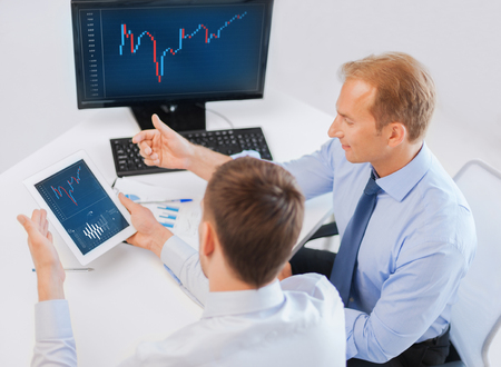 business, money and office concept - businessmen with notebook and tablet pc discussing forex chart on meeting photo