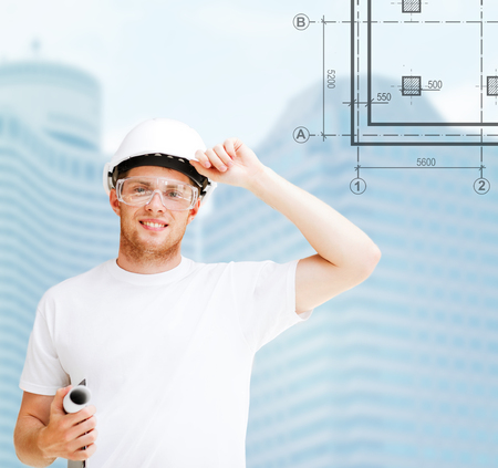 building, developing, consrtuction and architecture concept - male architect in helmet with blueprint and safety glasses photo