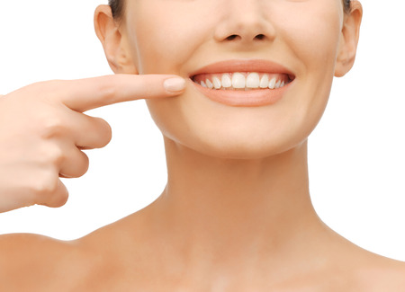 perfect teeth: beauty and dental health concept - closeup picture of beautiful woman pointing finger to her teeth