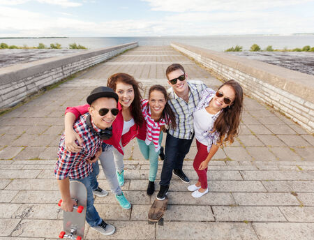 summer holidays and teenage concept - group of smiling teenagers with skates outside photo