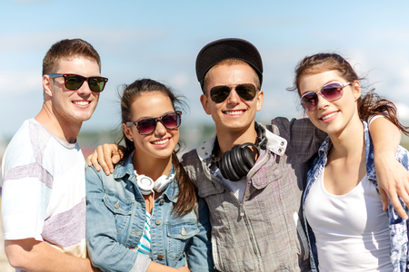 chilling out: summer holidays and teenage concept - group of smiling teenagers in sunglasses hanging outside