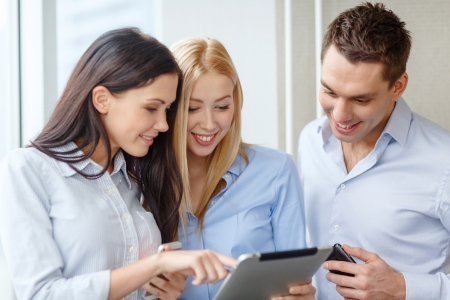 pcs: business and office concept - smiling business team working with tablet pcs and smartphones in office Stock Photo