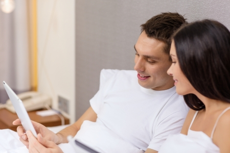 hotel, travel, relationships, technology, intermet and happiness concept - smiling couple in bed with tablet computer photo