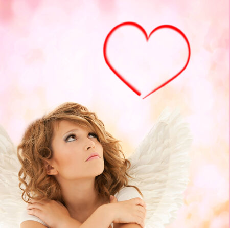 holidays, love and costumes concept - unhappy teenage angel girl over pink background photo