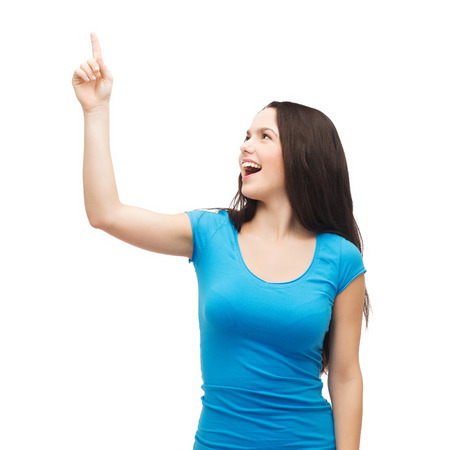 advertisement concept - attractive teenager in casual clothes pointing her finger up photo