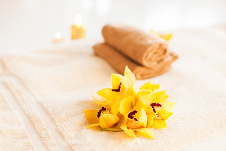 spa, health and beauty concept - closeup of towels, flowers and candles photo
