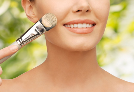 foundation: beauty amd make-up concept - closeup picture of beautiful woman with brush applying cream foundation