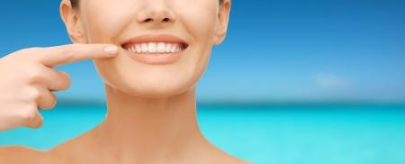 美容と歯科医療の概念 - 美しい女性彼女の歯にポインティング指のクローズ アップ写真 写真素材