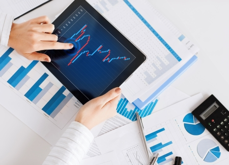 business, office, school and money concept - woman with chart paper, tablet pc and forex chart in it photo