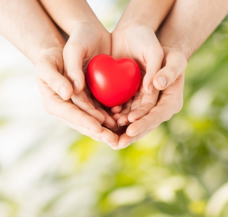 parents  love: family and love concept - close up of woman and man hands with heart