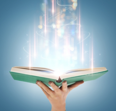 education and book concept - close up hand holding open book with magic lights photo