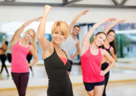 weight loss man: fitness, sport, training, gym and lifestyle concept - group of smiling people with trainer exercising in the gym