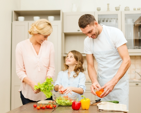 mixing: food, family, hapiness and people concept - happy family making dinner in kitchen Stock Photo