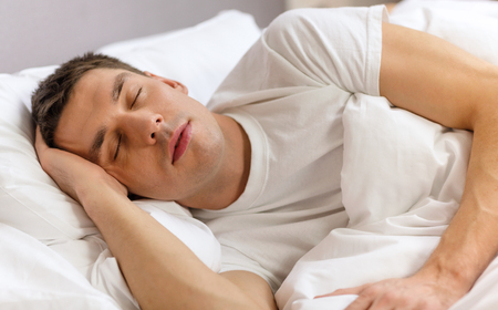 hotel, travel and happiness concept - handsome man sleeping in bed photo