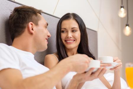 enamorados en la cama: hotel, viaje, las relaciones y el concepto de la felicidad - sonriente pareja de desayunar en la cama en la habitaci�n del hotel