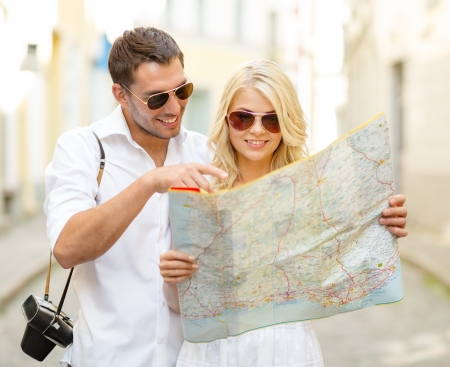 traveling: summer holidays, dating and tourism concept - smiling couple in sunglasses with map in the city Stock Photo