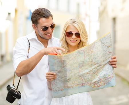 zomervakantie, dating en toerisme concept - glimlachend paar in zonnebril met kaart in de stad Stockfoto