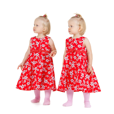 children and twins concept - two identical twin girls in red dresses looking somewhere photo