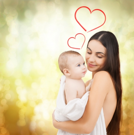family, children, parenthood and happiness concept - happy mother feeding her adorable baby Stock Photo
