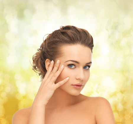 updo: health and beauty concept - face and hands of beautiful woman with updo