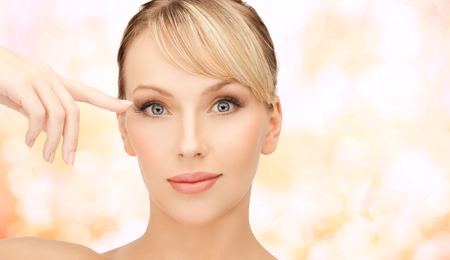 eyelid: health, spa and beauty concept - face of beautiful woman touching her eye area Stock Photo