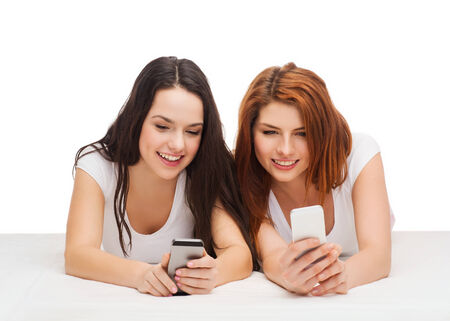 technology, friendship and people concept - two smiling teenagers with smartphones photo