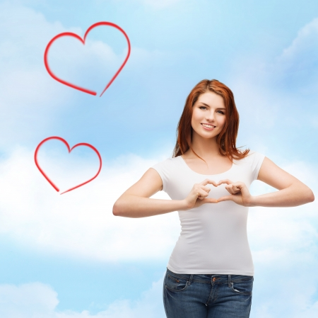 designe: friendship, t-shirt designe and happy people concept - smilinjg girl in white blank t-shirts showing heart with hands Stock Photo