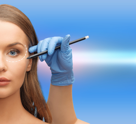 health, beauty and plastic surgery concept - woman face and beautician hands with pencil photo