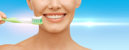 perfect teeth: beauty and dental health concept - beautiful woman with green toothbrush Stock Photo
