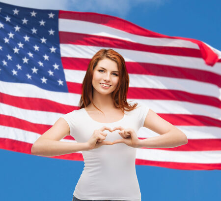 friendship, patriotic and happy people concept - smiling girl in white t-shirt showing heart with hands photo