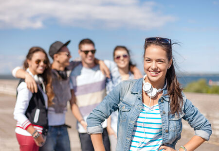 teenage love: summer holidays and teenage concept - teenage girl in sunglasses and headphones hanging out with friends outside