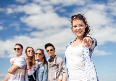 teenage love: summer holidays and teenage concept - teenage girl in sunglasses hanging out with friends outside and showing thumbs up