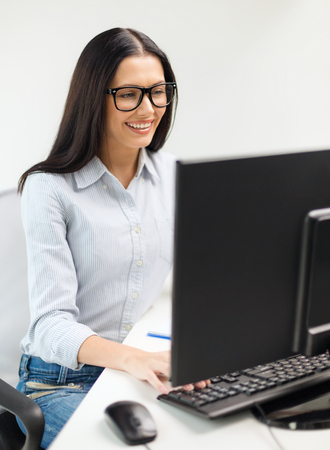 education, school, business and technology concept - smiling businesswoman or student wearing black eyeglasses photo