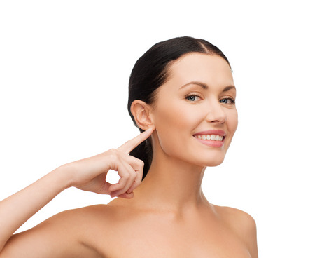health, spa and beauty concept - clean face of beautiful young woman pointing to her ear Stock Photo