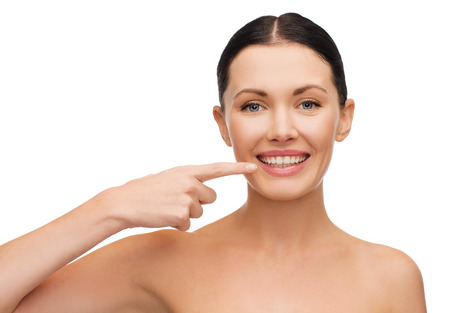 health, spa and beauty concept - clean face of beautiful young woman pointing to her mouth