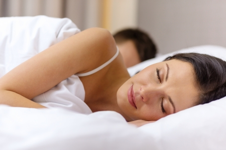 wife: hotel, travel, relationships, and happiness concept - happy couple sleeping in bed