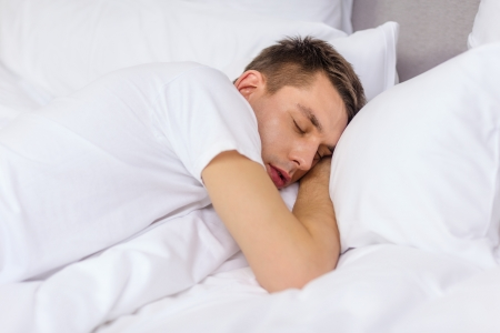sleeping room: hotel, travel and happiness concept - handsome man sleeping in bed Stock Photo