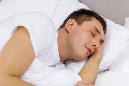 hotel, travel and happiness concept - handsome man sleeping in bed Stock Photo - 25507999