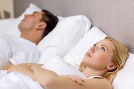 hotel, travel, relationships, and problems with sleep concept - family couple in bed, woman with insomnia photo