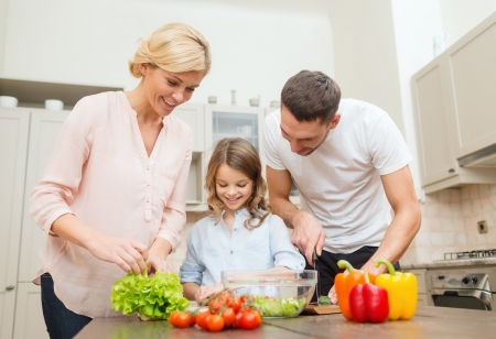 making: food, family, hapiness and people concept - happy family making dinner in kitchen Stock Photo