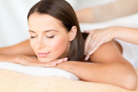 eye massage: health, beauty, resort and relaxation concept - beautiful woman with closed eyes in spa salon getting massage
