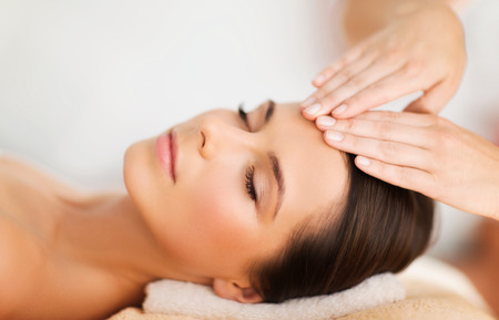 spa, resort, beauty and health concept - beautiful woman in spa salon getting face treatment photo