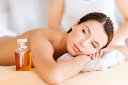 beauty and spa concept - beautiful woman in spa salon getting oil treatment photo