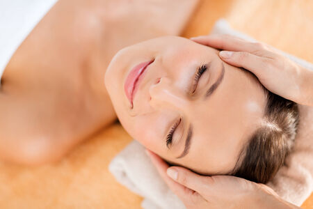 health, beauty, resort and relaxation concept - beautiful woman in spa salon getting face treatment photo